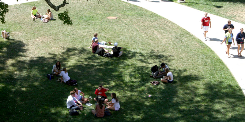 Aerial shot of students studying and relaxing in grass outside of the Farmer School of Business