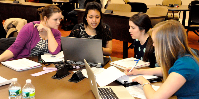 Four female students work together with laptops and notepads