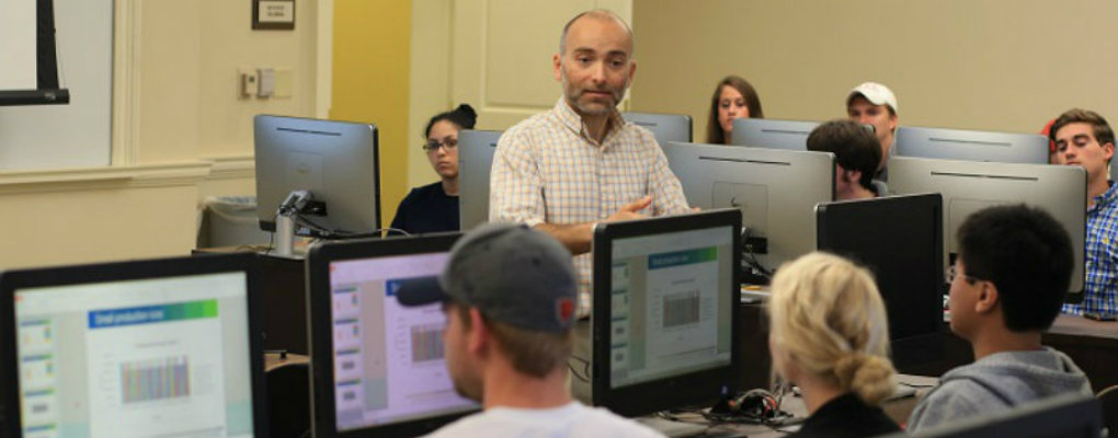 an image of Dr. Zafer teaching his class in a classroom with computers