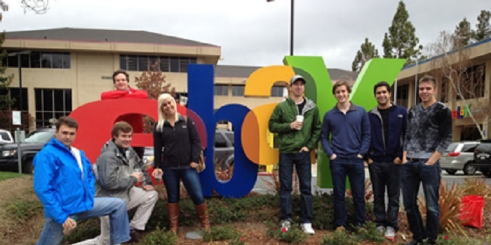 students stand in front of ebay logo