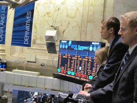 Students visit Wall Street. three students stand in front of a stock trading board.
