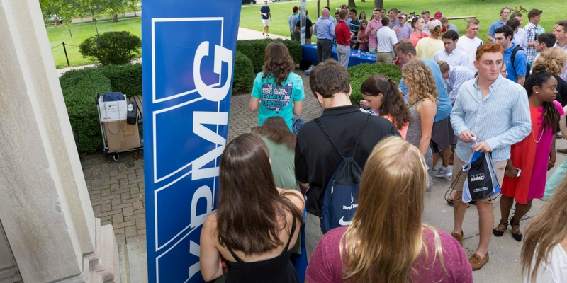 Students standing outside near a vertical KPMG sign
