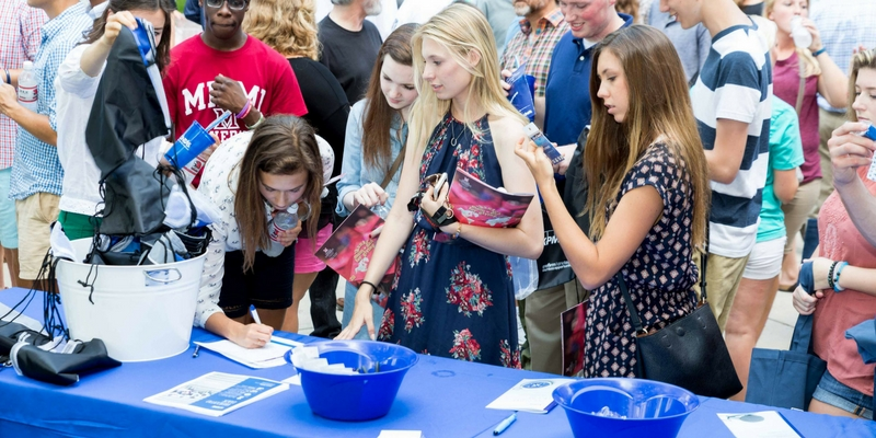 Students stand at a table with a blue tablecloth