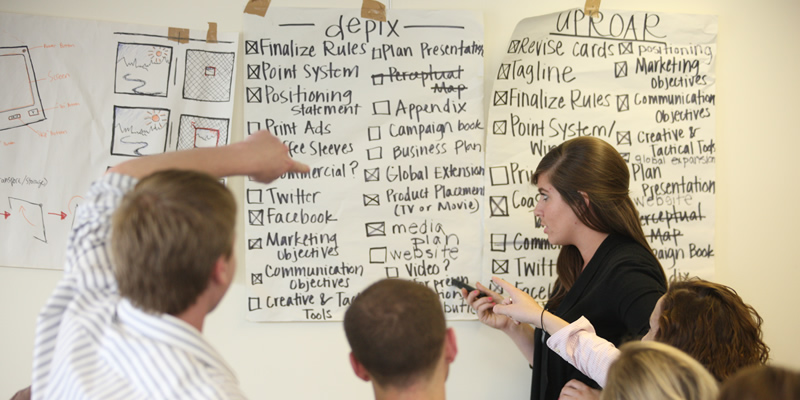 students working on a white board under two categories