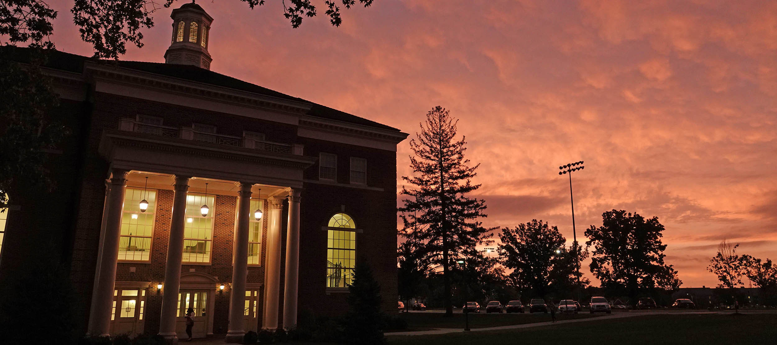 Taylor Auditorium during an orange-sky sunrise