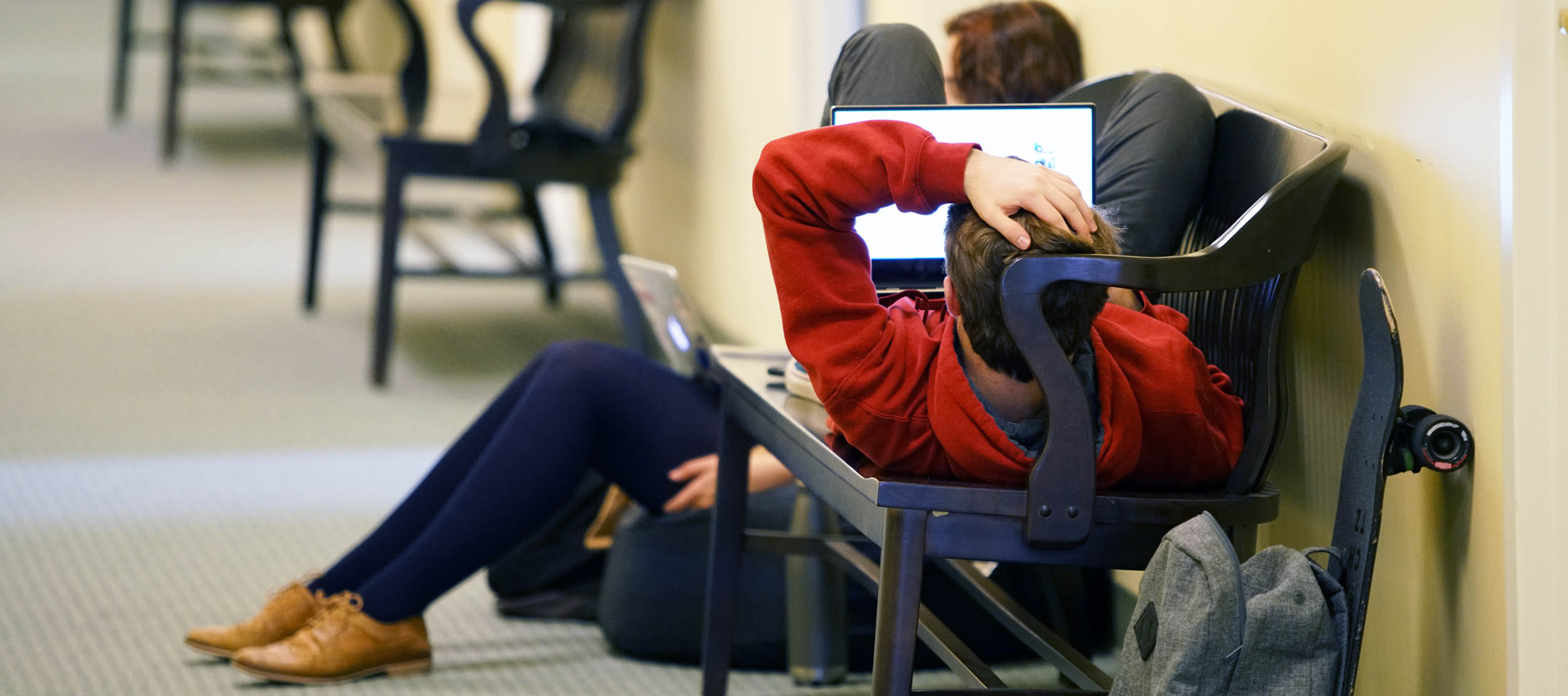 A student uses his laptop while reclined on a bench in a second-floor hallway