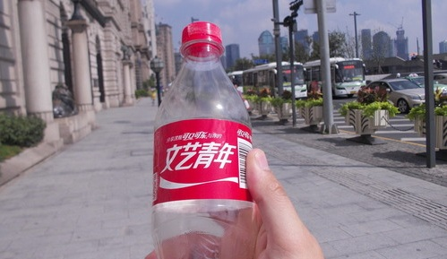 Chinese coca cola bottle in foreground, with a city street in the background