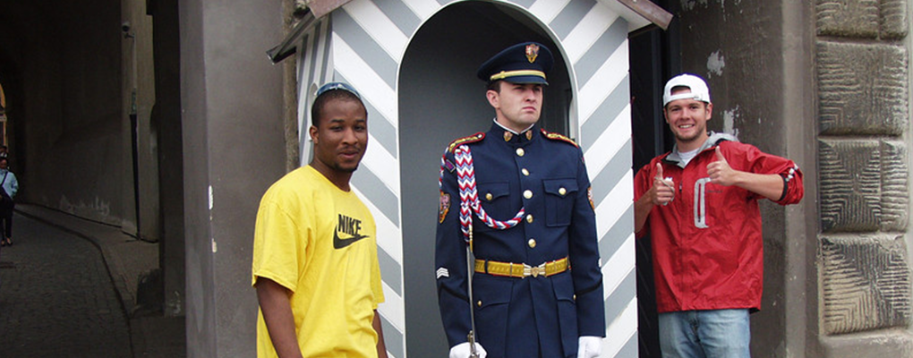Two students stand next to a straight-faced guard