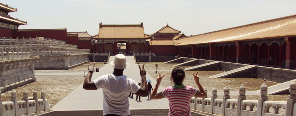 The back of two students making peace signs with their hands standing in the courtyard of a temple