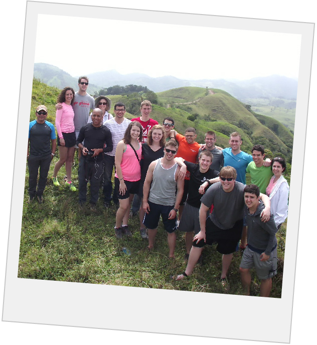 group of students posing on a large hill with hills and mountains in the background