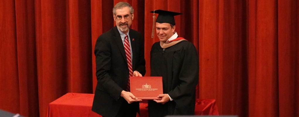 Dean Marc Rubin presents a diploma at graduation