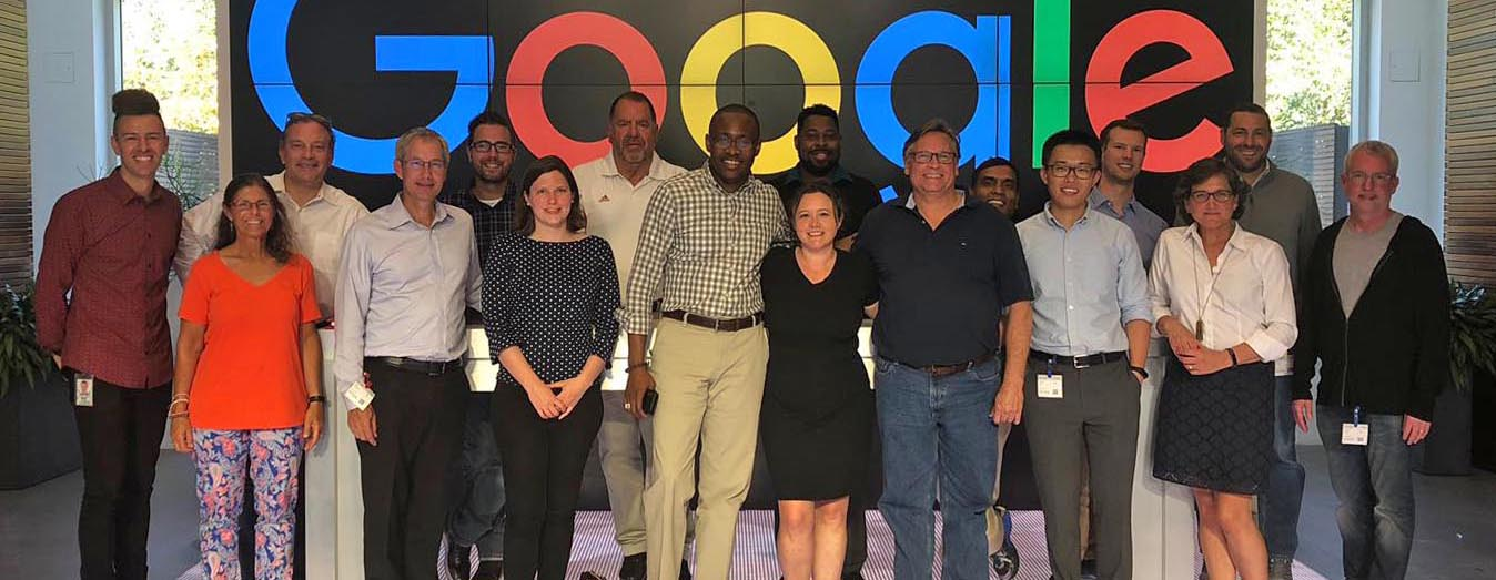Faculty pose for photo in front of Google sign