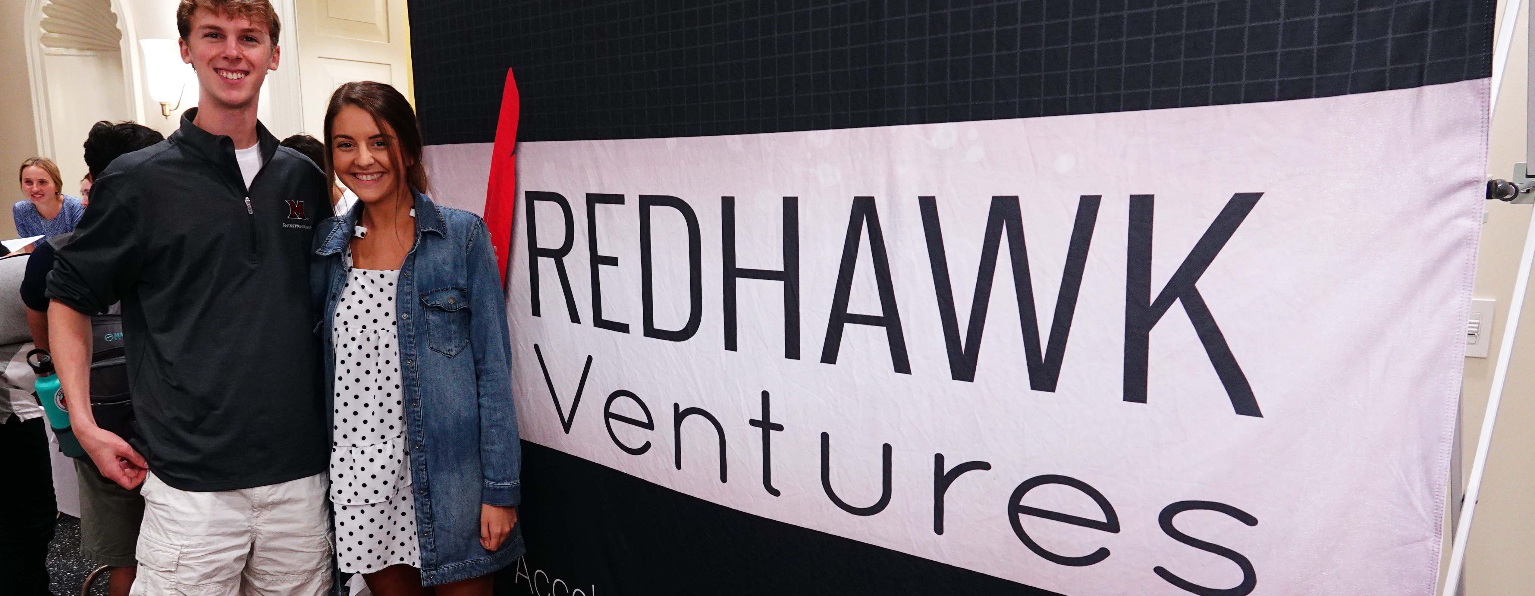 Laura Mena and Andy Newman pose by a Redhawk Ventures poster