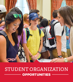 Students laugh together in the commons over a banner that says 'student organization opportunities'
