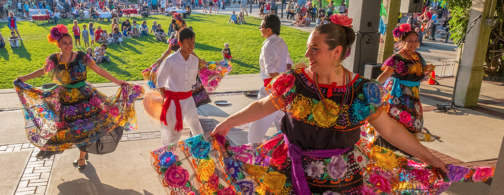 Mexican dance performers wearing traditional clothing perform on an outdoor stage
