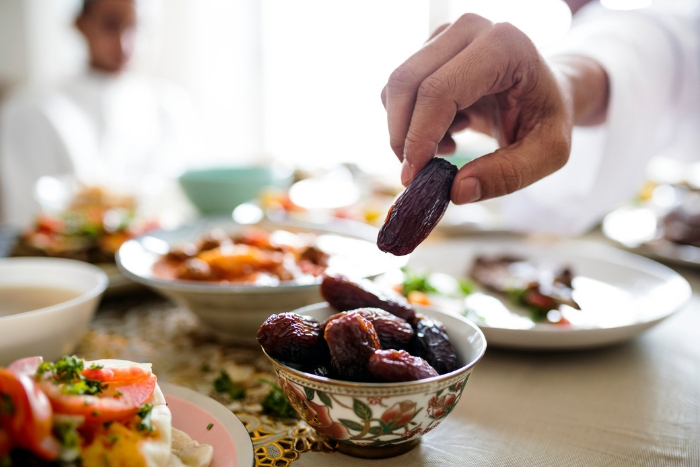 Middle Eastern Suhoor or Iftar meal, hand grabbing dates