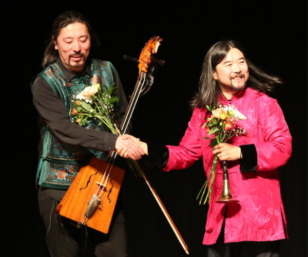 two performers shake hands. one of them holds their instrument while the other holds flowers