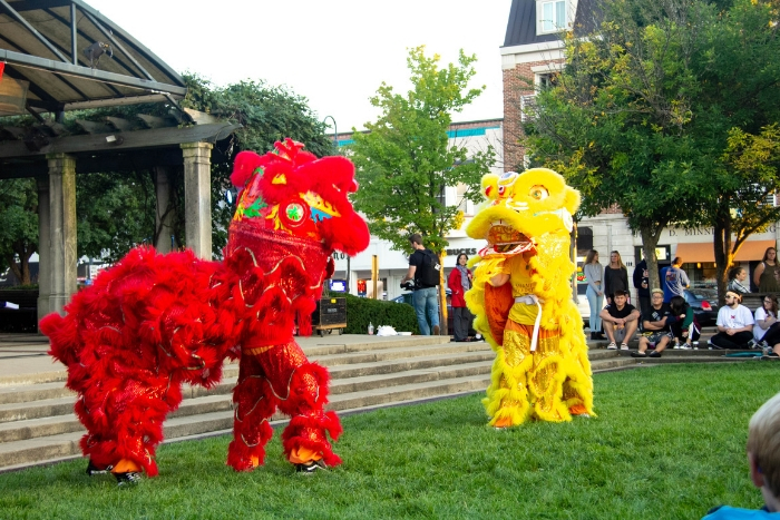 lion dance uptown at Chinese Festival, one lion is red and the other is yellow