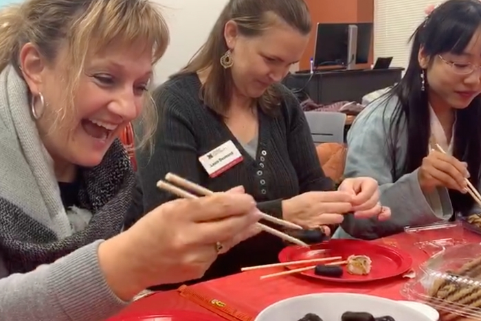 Miami staff and faculty learning how to use chopsticks