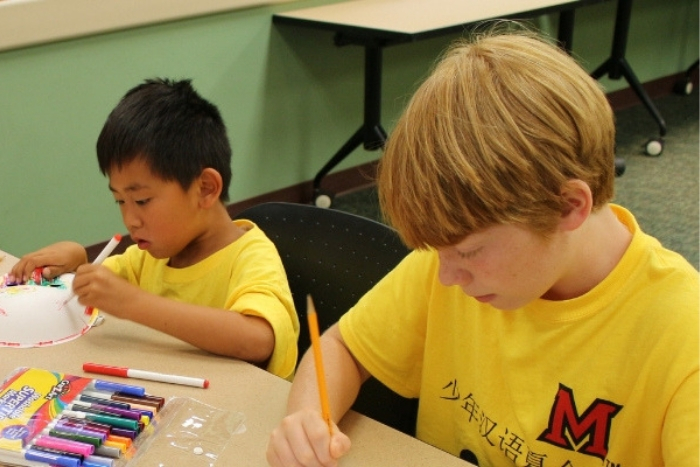 two local school students in yellow t-shirts working on Chinese crafts