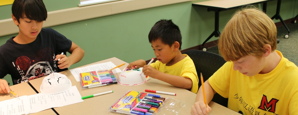 kids wearing yellow t-shirts, doing arts and crafts at a past Confucius Institute Kids Summer Camp