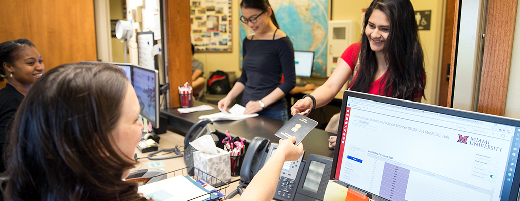 A student receives her passport from the passport service desk