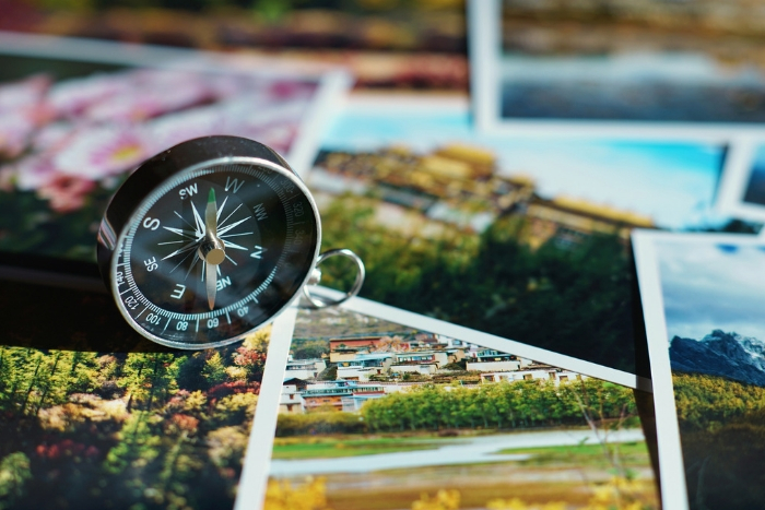 travel photos overlapping each other, compass on top that points to west
