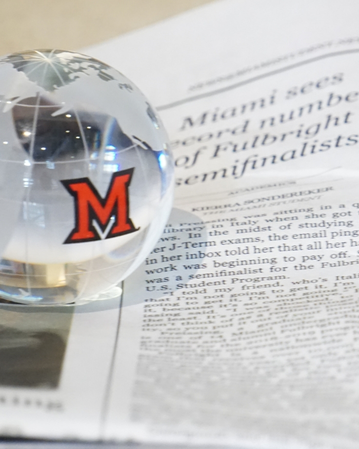 "image of globe paperweight with Miami ""M"" logo sitting on top of newspaper"