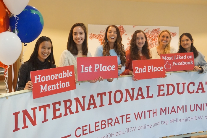 "students holding signs that say ""first place"", ""second place"", etc. in MacMillan Hall's lobby, red and white balloons, banner on stairwell that says ""International Education Week"""