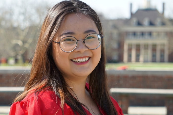 Headshot of Miami alum Sunny (Ni) Suo in front of MacMillan Hall in her red gown for graduation