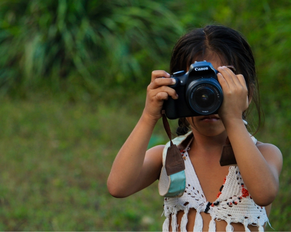 little girl with camera on her face, trying to take a photo