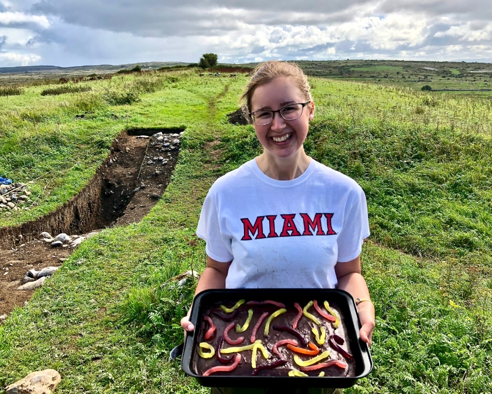 student in field with Miami t-shirt on, holding a dish of dessert with gummy worms on top