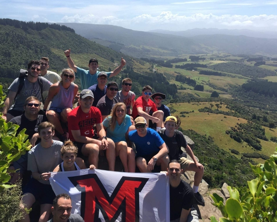 Group of Miami students holding Miami flag in front of a gorgeous scene on their study abroad program