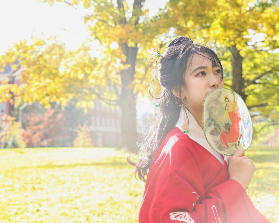 Miami international student from China in traditional Chinese clothing standing outside on Miami's campus in the fall, trees and leaves surround her with yellow and green colors