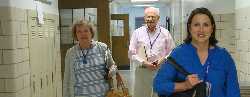 A group of retirees walk through the hallway before their class