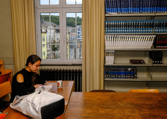 one student studying in the MUDEC library, view outside the window of town; buildings outside window have a European look and feel to them