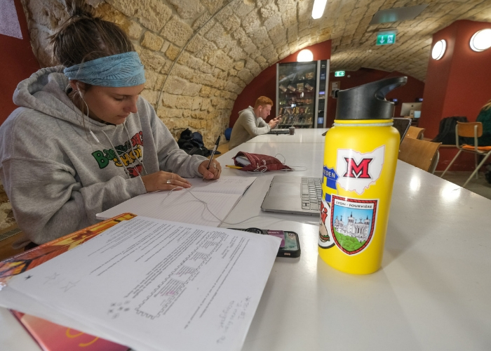student studying in cave of MUDEC with Bagel and Deli sweatshirt on