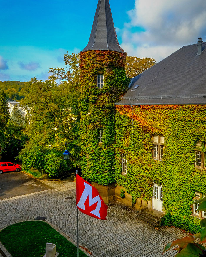 MUDEC Chateau in Luxembourg, bright blue sky, red Miami flag blowing in wind