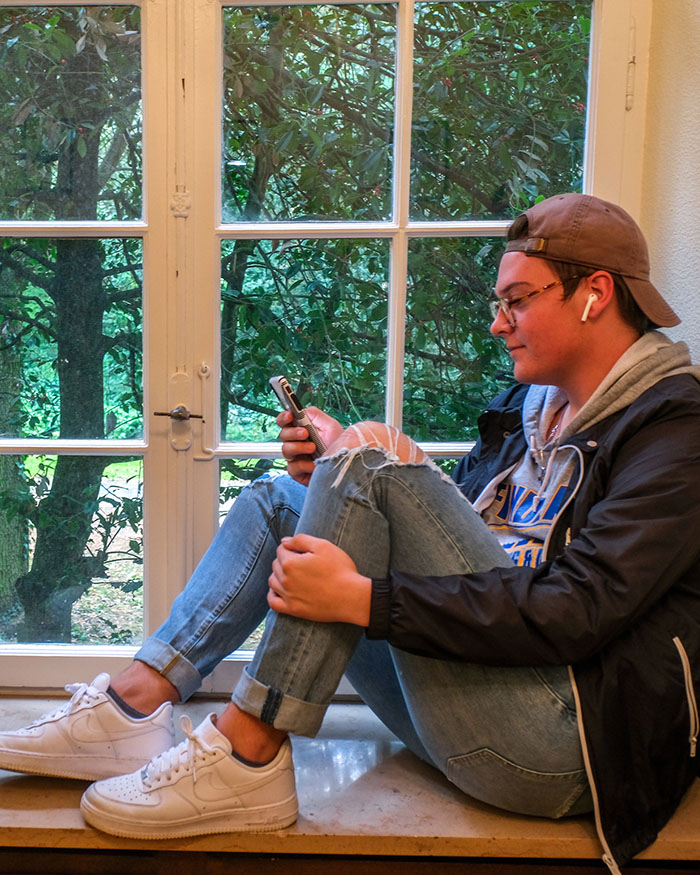 student sitting on ledge in front of window, on phone
