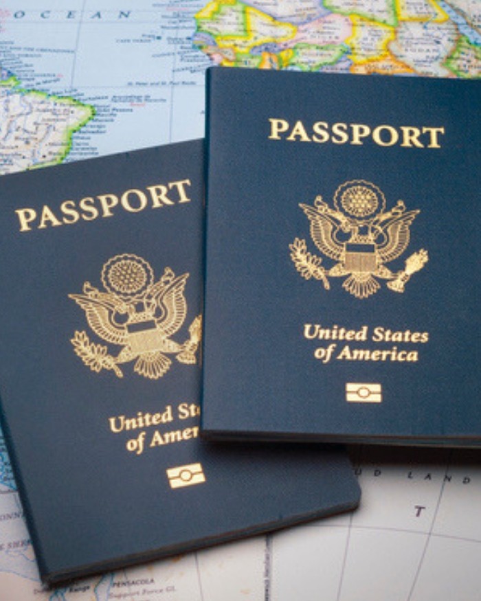 Two US passports laying on top of a world map