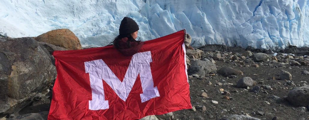 student holding Miami flag in front of glacier in Argentina