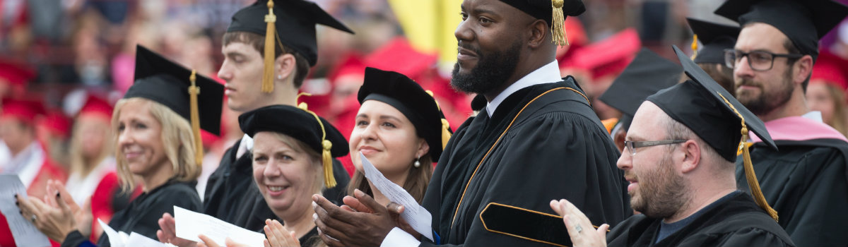Doctoral graduates at May commencement clapping