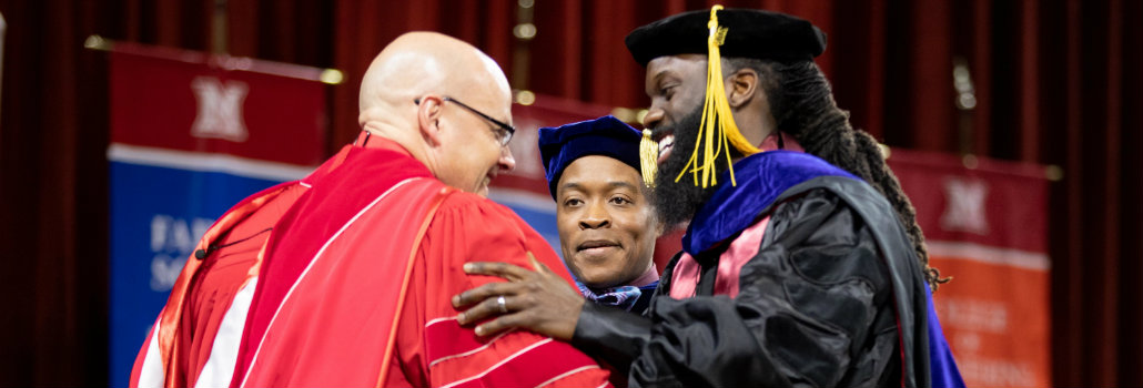 Picture of a doctoral student with their hooding professor, shaking hands with President Crawford at December graduation