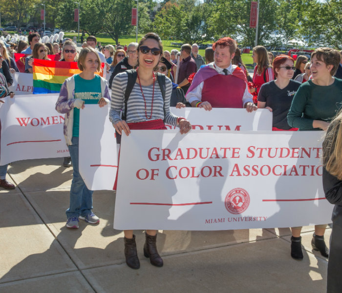 Students holding a banner with the Graduate Students of Color Association on the banner