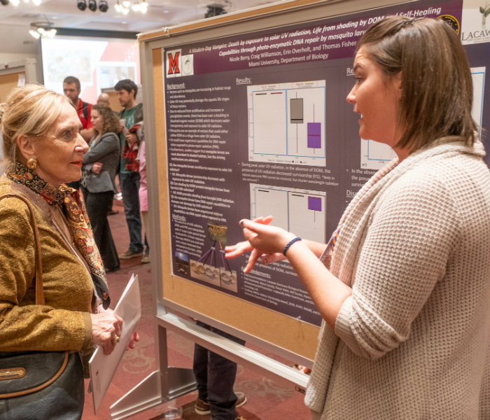Alumni Judge with a student in front of their research poster