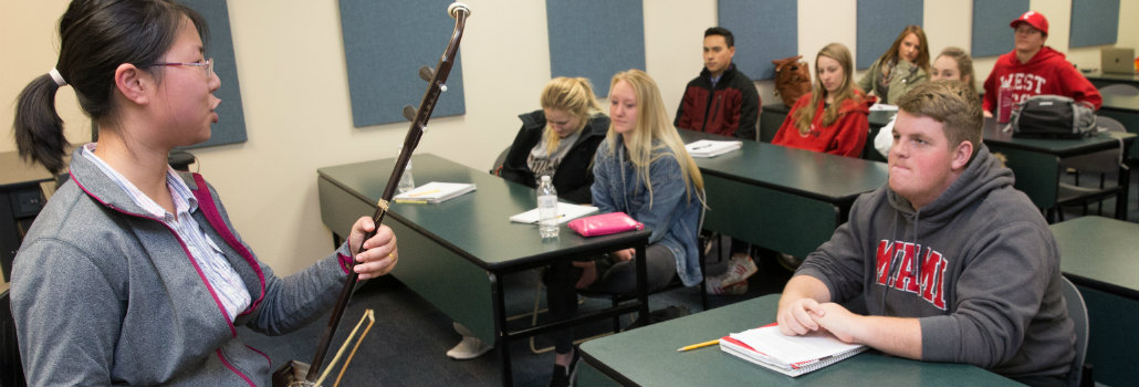 Student in front of a classroom discussing their instrument research