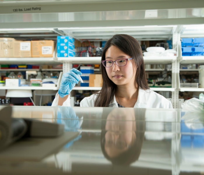 Girl holding a piece of research equipment in a lab