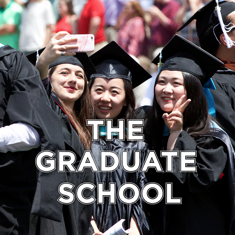 The Graduate School. Students in caps and gowns take a selfie at commencement.