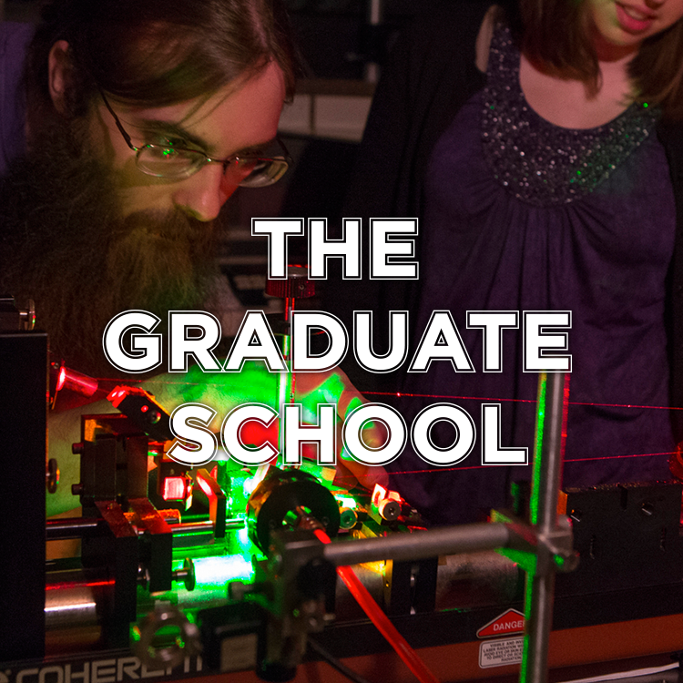 The Graduate School. Pictured: Male student works in a dark room using a laser printer. Three other students watch him.