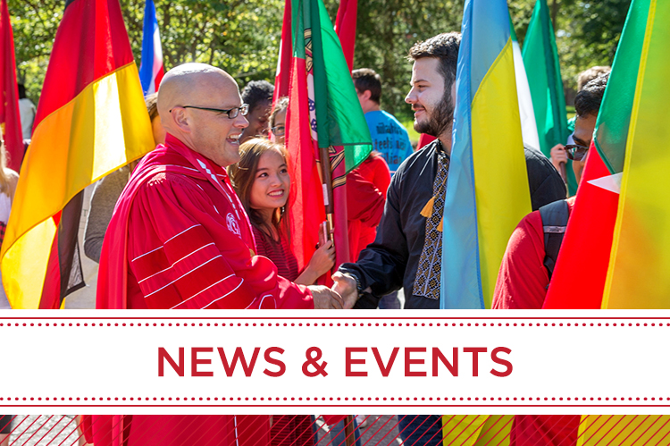 News and Events. Students holding flags shake hands with President Crawford